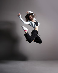 A young and fit brunette woman dancing in sporty clothes