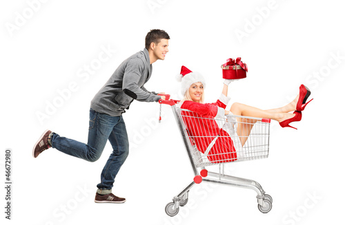 Guy pushing a female wearing christmas costume in a shopping car