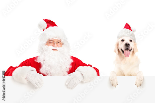 Santa Claus and dog posing behind a billboard