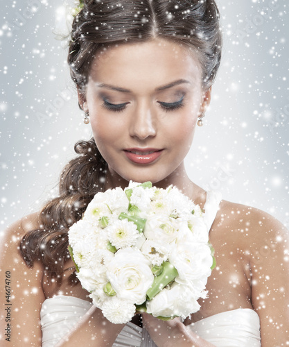 Portrait of a young bride holding a bouquet of flowers