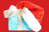 Santa Hat with a christmas gift over a red background