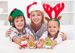 Happy woman with kids in christmas hats holding gingerbread peop