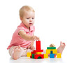 Child girl playing toy blocks and building tower. Isolated on wh