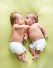 funny twins brothers babies lying on green