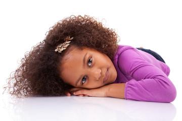 Cute little African Asian girl lying down on the floor
