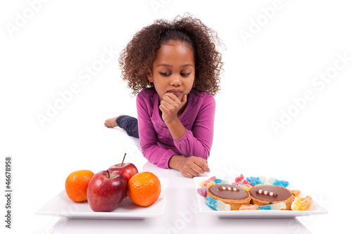 Little African Asian girl hesiatating between fruits or  candy