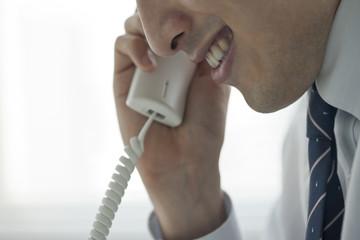 不気味な笑みを浮かべ電話をする男性