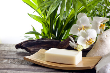 Spa soap and white orchids on stone against palm