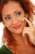 Beautiful redhair woman applying cream on a face