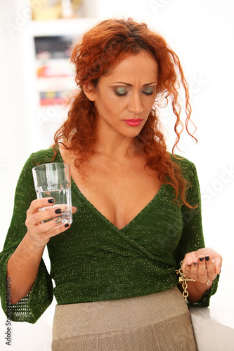Beautiful redhead woman drinking medicine