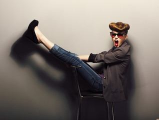 Funny girl  in sunglasses on chair in studio - vintage