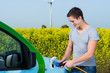 junger mann betankt ein elektromobil