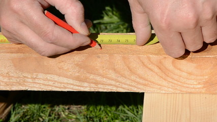 carpenter measure new wooden plank