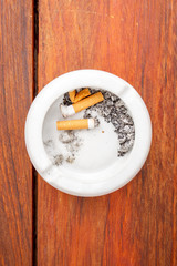 Smoked cigarettes in white ashtray