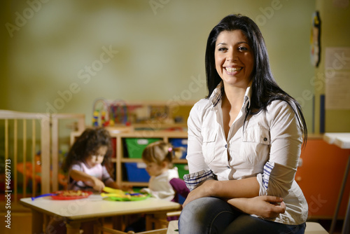happy teacher with children eating in kindergarten