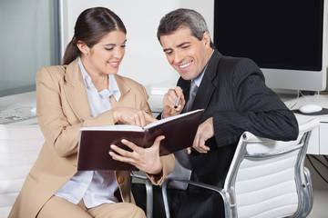 Geschäftsleute schauen in Auftragsbuch