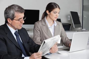 Frau am Laptop und Mann liest Zeitung