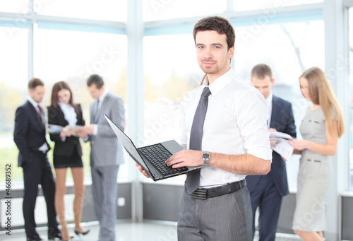 Smart business man using laptop with colleagues