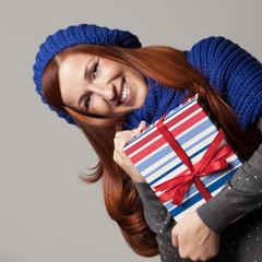Frau mit blauer Mütze hält ein Geschenk