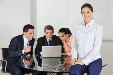 Lachende Frau mit Team im Büro