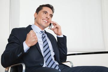 Jubelnder Manager mit Smartphone