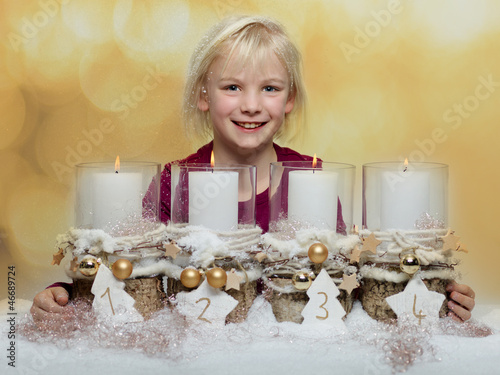 Cute blond child with Advent wreath waiting for christmas