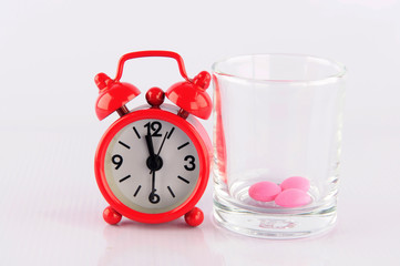 Red clock and medicine glass on white background