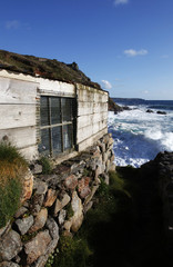 Fishing hut being battered by waves