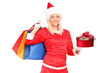 A female in christmas costume holding a gift and shopping bags