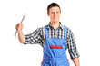 A repairman in overall holding a wrench and toolbox