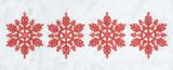 Four decorative Christmas snowflakes closeup on snow.