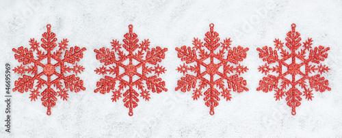 Four decorative Christmas snowflakes closeup on snow. - 46695969