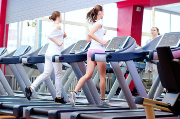 Two young sporty women run on machine