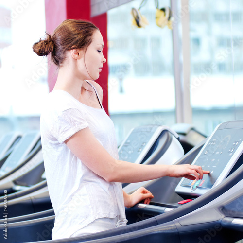 Young sporty woman run on machine