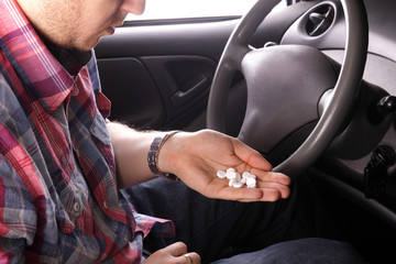Man sip tablets in the car
