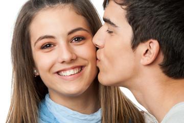 Boyfriend kissing girlfriend on cheek.