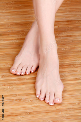 Well-groomed female feet on wooden floor.
