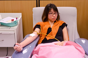Thai girl is donating blood in the red cross institution