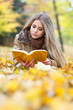 Cute young woman reading in a park in autumn