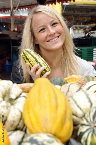 Junge Frau kauft Kürbis auf Markt