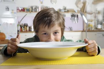 Kind hinter großem Teller