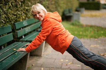 Ältere Dame macht Liegestütze im Park