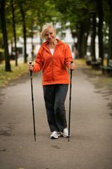 Ältere Dame beim Walken im Park