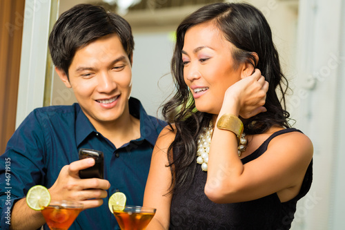 Asian man is flirting with woman in bar