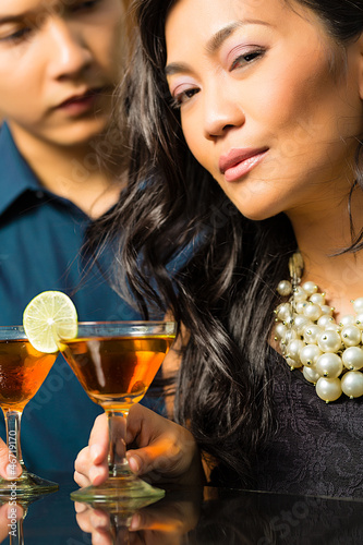 Man and woman in asia at bar with cocktails