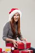 Frau sitzt neben vielen Weihnachtsgeschenken