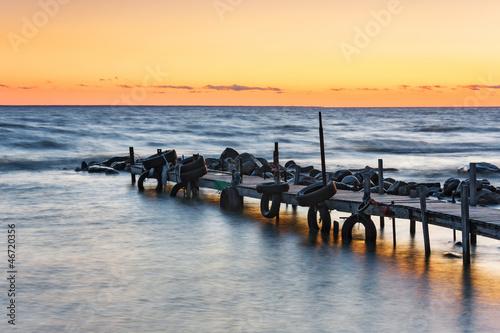 Zachód słońca na morzu łodzi za mostem