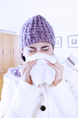 Woman with flu blowing nose at home
