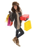 Woman in winter clothes with gifts and shopping bags smiling