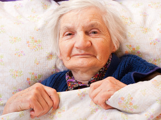Elderly lonely woman rests in the bed
